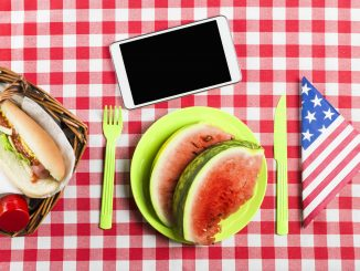 Memorial Day Remote Jobs - Red and white checked table cloth over table with American flag napkin folded into a triangle and Memorial Day cookout food. A phone sits on the table above the plate of watermelon.