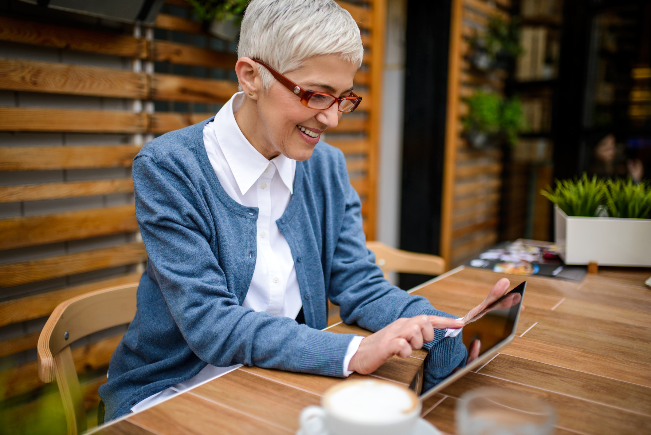 smiling mature professional woman using tablet and drinking coffee - Top 20 Remote Work States in 2018 - Virtual Vocations telecommute and remote jobs