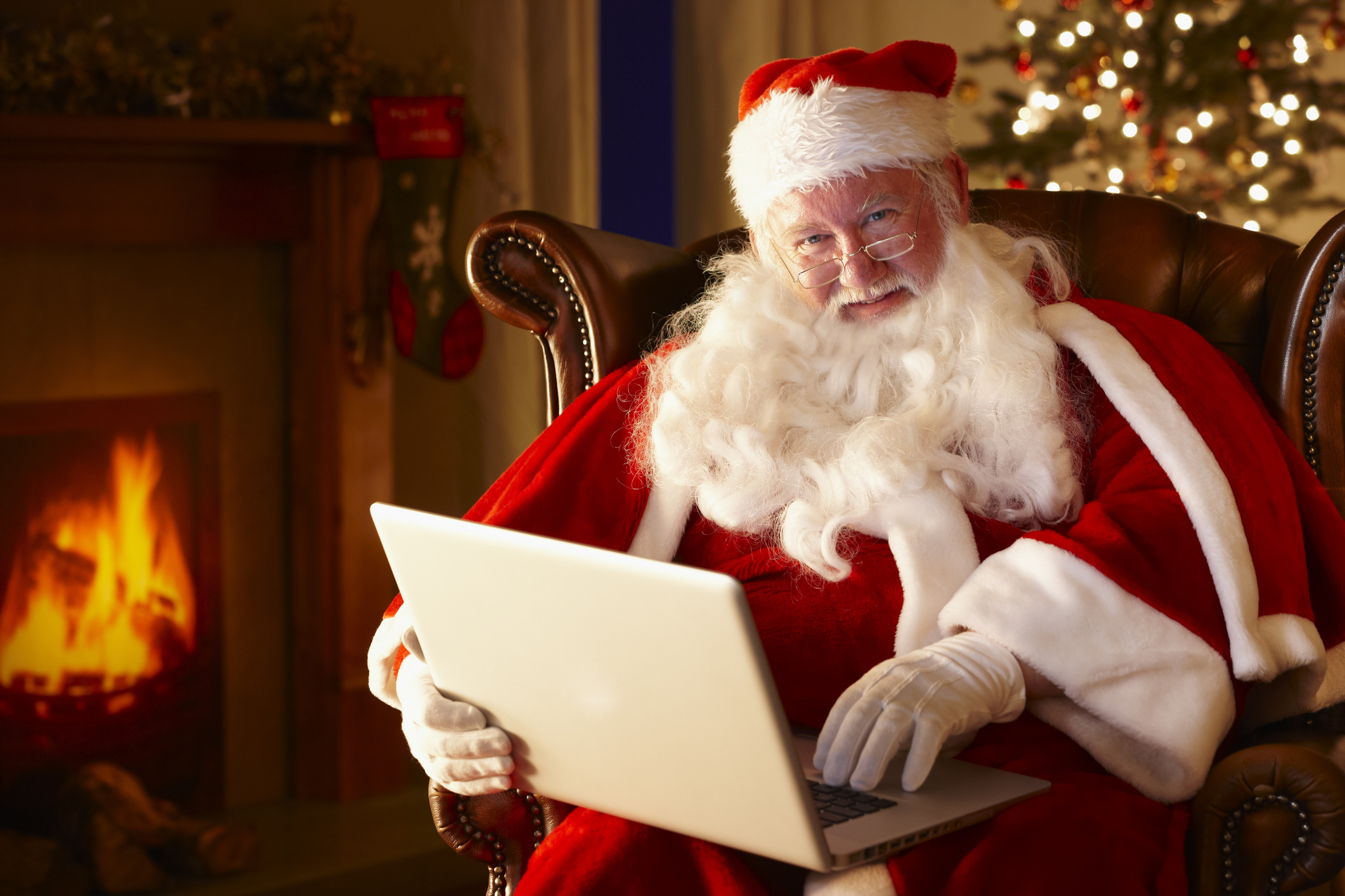 Santa using computer by fireplace - winter remote jobs - Virtual Vocations telecommute and remote jobs