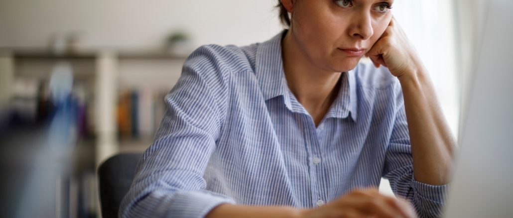 Woman struggling and frustrated with remote work on her laptop